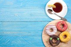 Verglaasd donuts met een kop thee op een blauwe houten achtergrond met exemplaarruimte voor uw tekst Hoogste mening royalty-vrije stock afbeeldingen