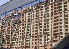 Verglaasde blauwe de bouwmuur met een bezinning van het huis Stock Afbeeldingen