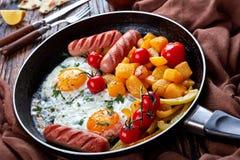 Verglaasde pompoen, gebraden eieren, worsten, in een koekepan stock foto's