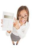 Vergnügte Frau des Buchhalters, die auf einen Taschenrechner zeigt Stockbild