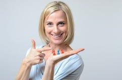 Vergnügte Frau, die auf drei meeples zeigt Lizenzfreies Stockbild