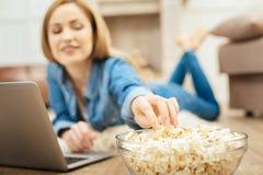 Vergnügte Frau, die Popcorn auf dem Boden isst Lizenzfreie Stockbilder