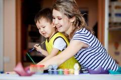 Vergnügte Kindheit, ein kleiner Junge, der mit seiner Mutter spielt, zeichnet, Farben auf den Palmen stockfotos