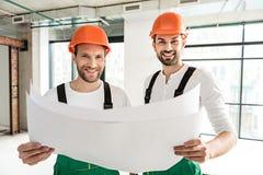 Vergnügte lächelnde Erbauer, die Papiere halten lizenzfreie stockbilder