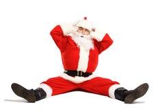 Vergnügte und lustige Santa Claus beim Sitzen verwirrt Lizenzfreies Stockfoto