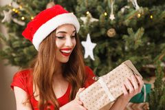 Vergnügte Weihnachtsfrau, die Geschenk Santa Hat Surprised Ofs A trägt lizenzfreie stockfotos