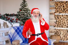 Vergnügter Vater Christmas, das telefonisch Eltern anruft Stockbild