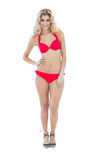 Vergnügtes blondes Modell, das mit der Hand auf den Hüften tragen roten Bikini aufwirft Lizenzfreie Stockfotografie
