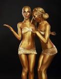 Vergoldung. Färbung. Zwei lustige Frauen mit Malerpinsel. Goldenes Make-up Lizenzfreie Stockfotos
