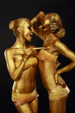 Vergoldung. Zwei lustige Frauen mit Malerpinsel. Futuristisches glattes Goldmake-up Stockbilder