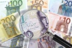 Vergrößerungsglas über Euroanmerkungen. Deutsche Mark im Vordergrund Stockbild