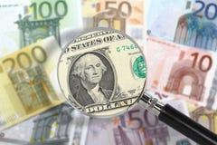 Vergrößerungsglas über Euroanmerkungen. US-Dollar im Vordergrund Stockbild