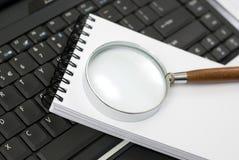 Vergrößerungsglas auf einem Notizblock Lizenzfreies Stockbild