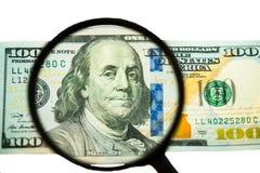 Vergrößerungsglas auf Geld Lizenzfreie Stockfotografie