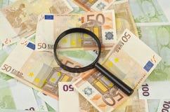Vergrößerungsglas auf Geldhintergrund Lizenzfreies Stockfoto