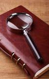Vergrößerungsglas auf Notizbuch Lizenzfreies Stockbild