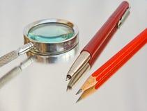 Vergrößerungsglas, Biro und Bleistift. lizenzfreie stockfotografie