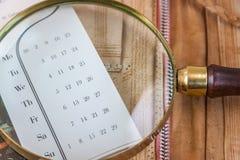 Vergrößerungsglas, das auf dem Kalender liegt Lizenzfreie Stockfotografie