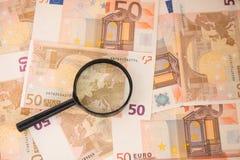 Vergrößerungsglas gerichtet auf Europa Euroanmerkungen mit Reflexion Vergrößerungsglas auf Eurobargeld Lizenzfreies Stockfoto