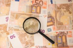 Vergrößerungsglas gerichtet auf Europa Euroanmerkungen mit Reflexion Vergrößerungsglas auf Eurobargeld Lizenzfreie Stockbilder