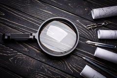 Vergrößerungsglas, Kompassse und Rollen von der Zeichnung auf einem schwarzen hölzernen Hintergrund lizenzfreies stockfoto