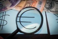 Vergrößerungsglas konzentrierte sich auf das Eurozeichen, auf einem Hintergrund des Euros, Dollar, reminbi Banknoten Stockbilder