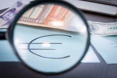 Vergrößerungsglas konzentrierte sich auf das Eurozeichen, auf einem Hintergrund des Euros, Dollar, reminbi Banknoten Stockfotos