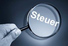 Vergrößerungsglas mit deutschem Wort Steuer Stockfotografie