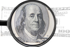 Vergrößerungsglas mit Dollar Stockfotos