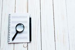 Vergrößerungsglas, Notizbuch, Stift auf einem weißen hölzernen Hintergrund lizenzfreie stockfotografie