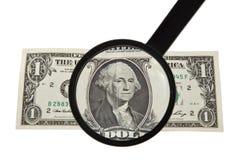 Vergrößerungsglas und ein Dollar Stockfotos