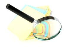 Vergrößerungsglas und ein Stapel Papier Lizenzfreies Stockfoto
