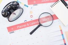 Vergrößerungsglas und Geschäft tragen Planer 2017 auf Schreibtischbüro ein Lizenzfreie Stockbilder