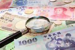 Vergrößerungsglas und Hintergrund des asiatischen Bargeldes Stockbilder
