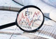Vergrößerungsglas und Kurse von ETF, von Kapitalien und von Aktien stockfotografie