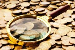 Vergrößerungsglas und Münzen stockfoto