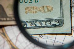 Vergrößerungsglas- und Papierwährung Stockfoto