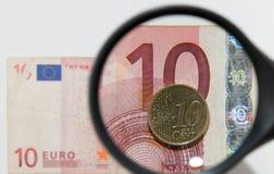 Vergrößerungsglas- und Papierwährung Stockfotografie