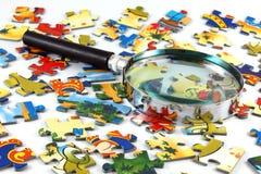 Vergrößerungsglas und Puzzlespiel Lizenzfreie Stockfotografie