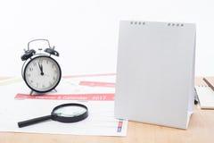 Vergrößerungsglas und Uhr mit Geschäft tragen Planer 2017 auf Schreibtischbüro ein Stockbilder