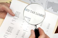 Vergrößerungsglas, welches die WortSteuerschuld auf Finanzpapier zeigt Stockfotografie