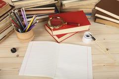 Vergrößerungsglasglas, farbige Bleistifte in einer hölzernen Schale, Notizbuch, Retro- Stift mit Stift und altes Porzellantintenf Stockfotos