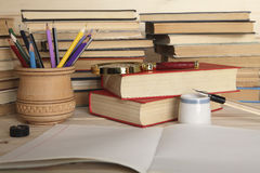 Vergrößerungsglasglas, farbige Bleistifte in einer hölzernen Schale, Notizbuch, Retro- Stift mit Stift und altes Porzellantintenf Stockfotografie