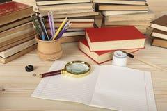 Vergrößerungsglasglas, farbige Bleistifte in einer hölzernen Schale, Notizbuch, Retro- Stift mit Stift und altes Porzellantintenf Lizenzfreie Stockfotos