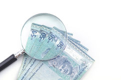 Vergrößerungsglasglas und -geld auf weißem Hintergrund Feder, Brillen und Diagramme Lizenzfreies Stockfoto