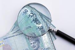 Vergrößerungsglasglas und -geld auf weißem Hintergrund Feder, Brillen und Diagramme Stockbilder