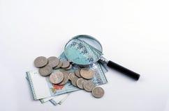Vergrößerungsglasglas und -münze auf weißem Hintergrund Feder, Brillen und Diagramme Stockbilder