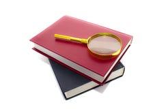 Vergrößerungsglasobjektiv und Stapel der Bücher Stockfotos