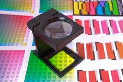 Vergrößerungsglas auf Farbenanleitung und -muster Lizenzfreie Stockbilder