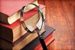Vergrößerungsglas mit alten Büchern Lizenzfreies Stockbild